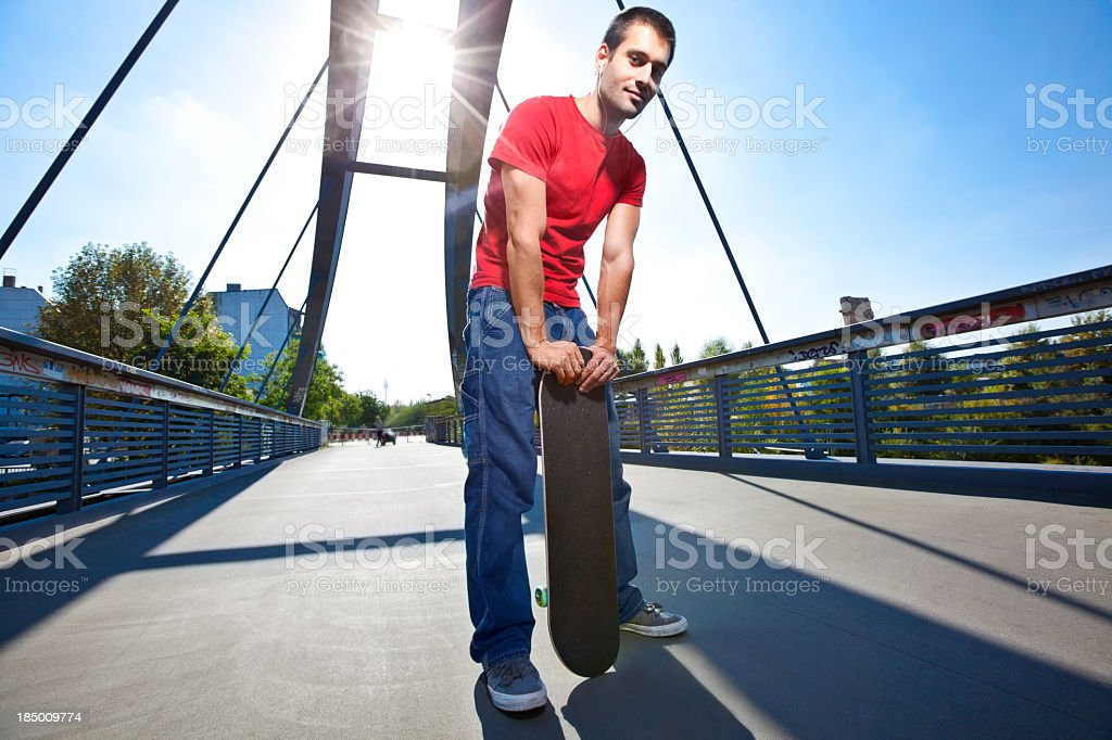 Young man holding skateboard stock photo