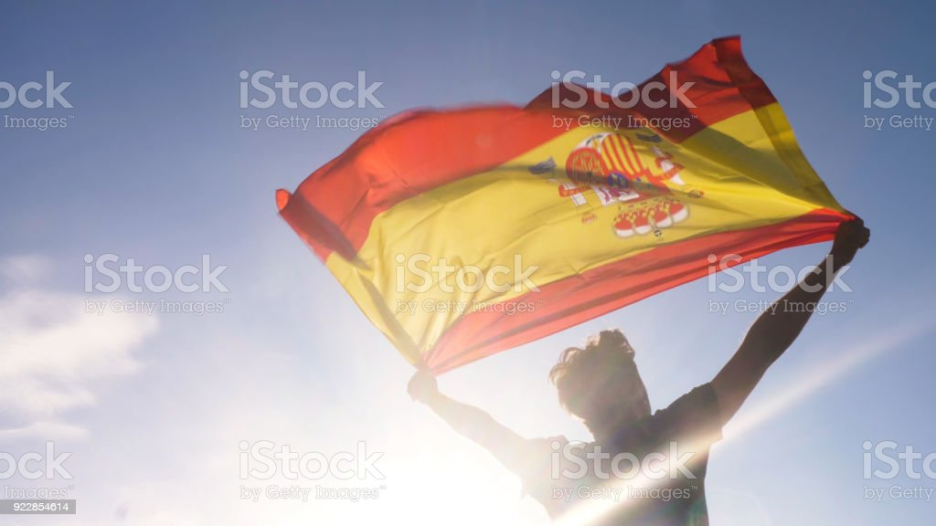 Young man holding spanish national flag to the sky with two hands at the beach at sunset spain - foto stock