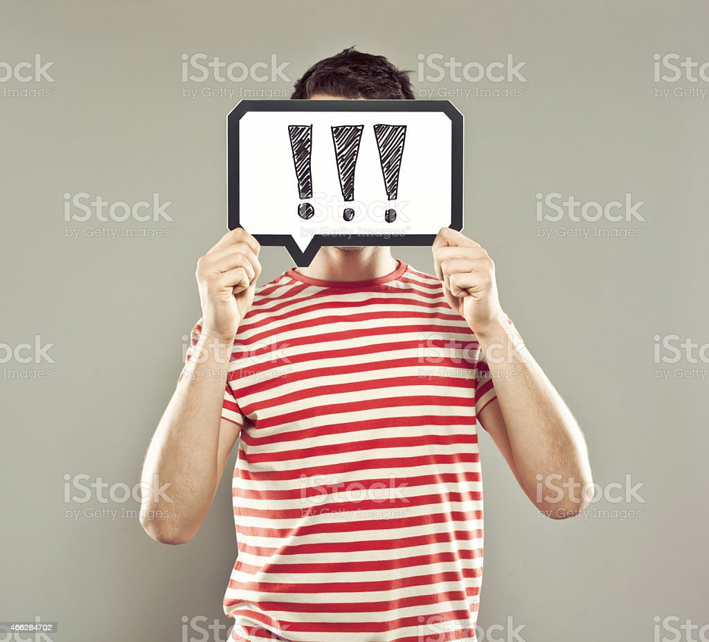 Young man holding speech bubble with exclamation marks stock photo