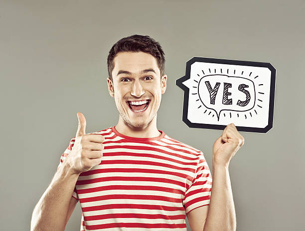 Young man holding speech bubble with text yes stock photo