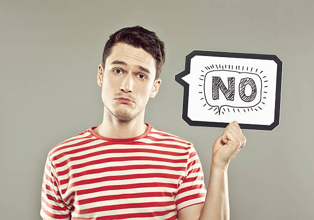 Young man holding speech bubble with word no Portrait of sad young man wearing striped t-shirt, holding a speech bubble with drawn word, looking at camera. Studio shot, grey background. single word no stock pictures, royalty-free photos & images
