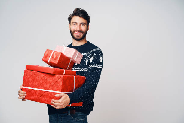 Young man holding stack of Christmas presents, smiling at camera, isolated. stock photo
