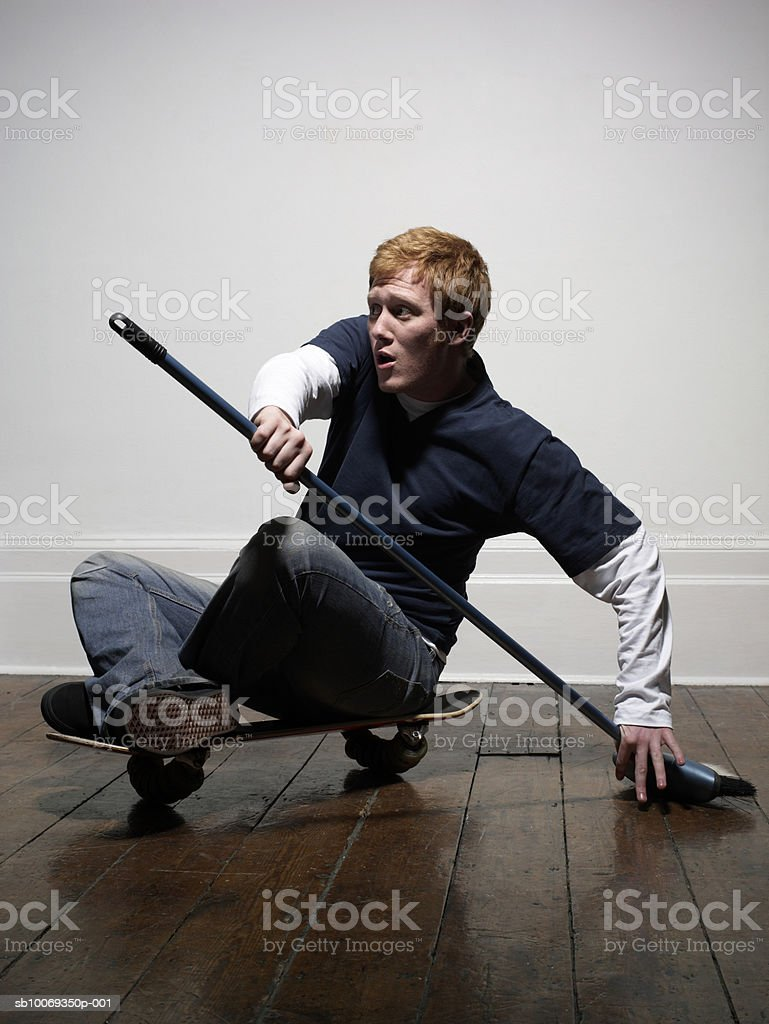 Young man holding sweeping brush on skateboard, indoors royalty-free stock photo