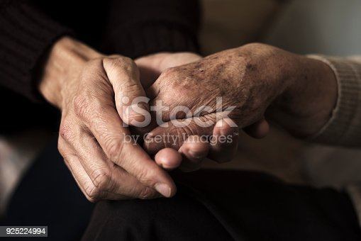 istock young man holding the hand of an old woman 925224994
