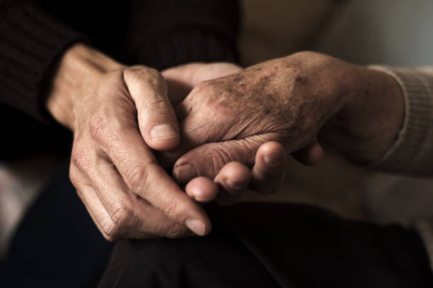 young man holding the hand of an old woman closeup of a young caucasian man holding the hand of an old caucasian woman with affection aging stock pictures, royalty-free photos & images
