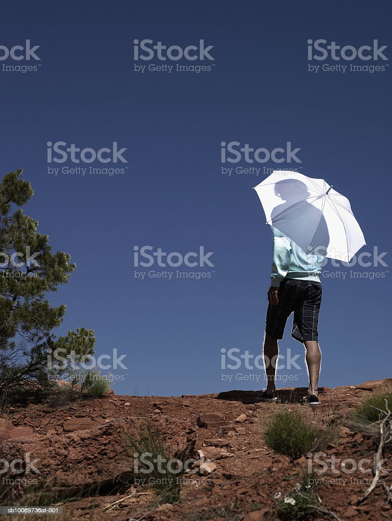 Young man holding umbrella, rear view royalty-free stock photo