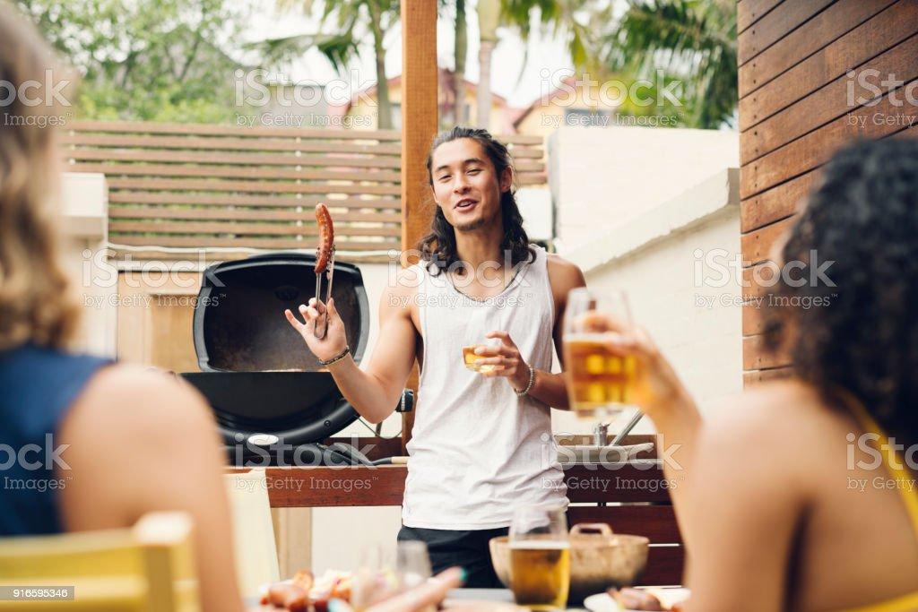 Jeune homme brandissant des saucisses devant le barbecue avec des amis sur le premier plan - Photo