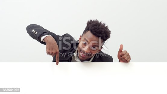 istock young man holding white board showing page 635904976