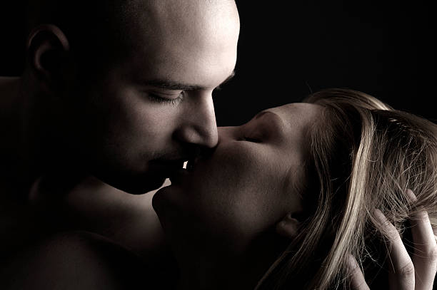 Young Man Holding Woman's Head and Kissing Her, Low Key stock photo