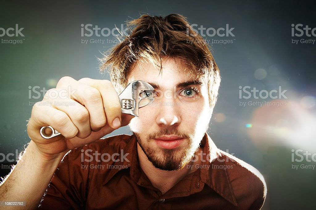 Young Man Holding Wrench In Front of Face royalty-free stock photo