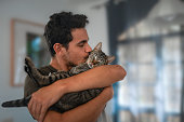 istock young man holds a tabby cat in his arms and kisses it 1281620747