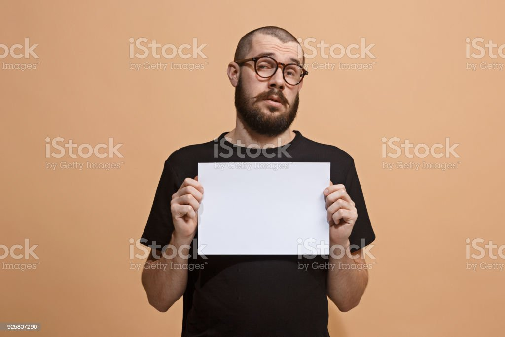 A young man holds an empty plate in his hands to fill your text. Emotional, courageous face stock photo