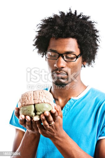 613542420 istock photo Young man holds anatomical model of human brain carefully 185329054