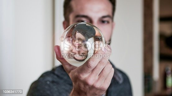 istock Young man holds crystal ball in front of face 1036341770