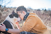 Young Man Hugging and Kissing His Dog in Nature .