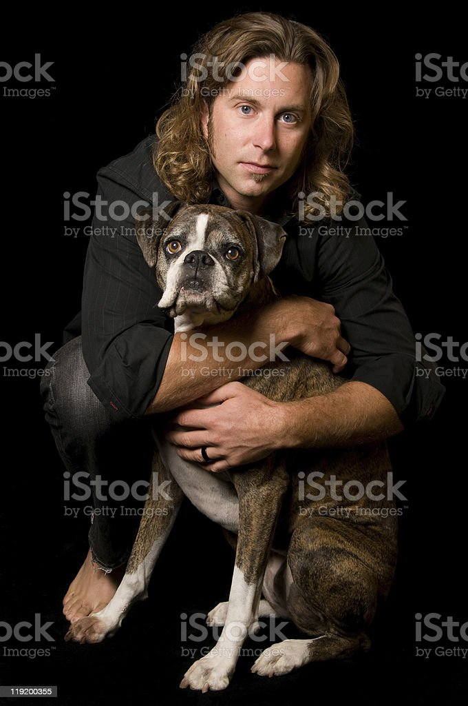 Young Man Hugging Cute Boxer Dog stock photo