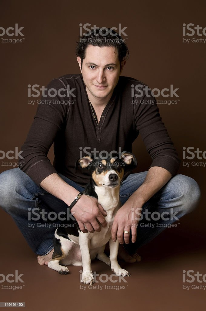 Young Man Hugging Jack Russell Terrier Dog stock photo