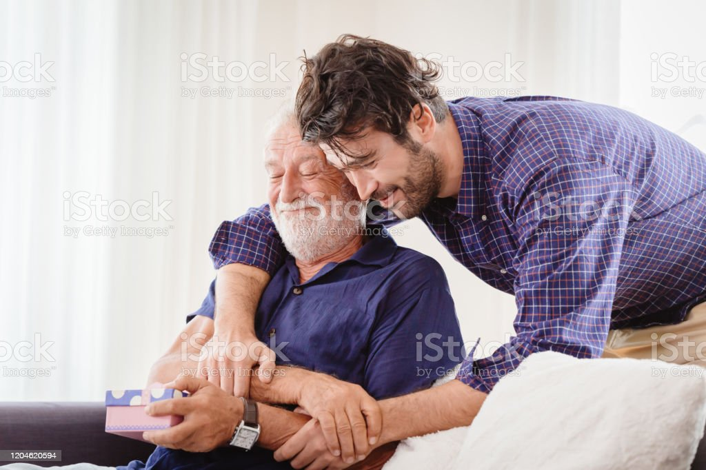 Young Man Hugs The Uncle Old Man Warmly Inside The House Son Happy And Love His Father Or Grand Father With Gift Box Concept Stock Photo Download Image Now Istock