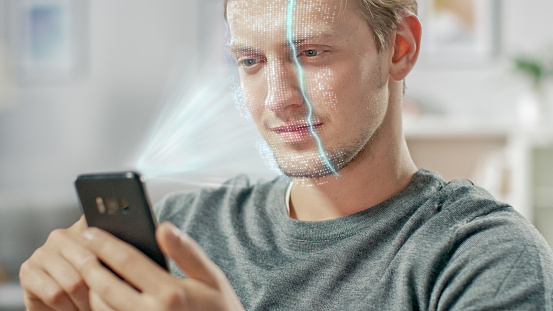 istock Young Man Identified by Biometric Facial Recognition Scanning Process from His Smartphone. Futuristic Concept: Projector Identifies Individual by Illuminating Face by Dots and Scanning with Laser 1159763174