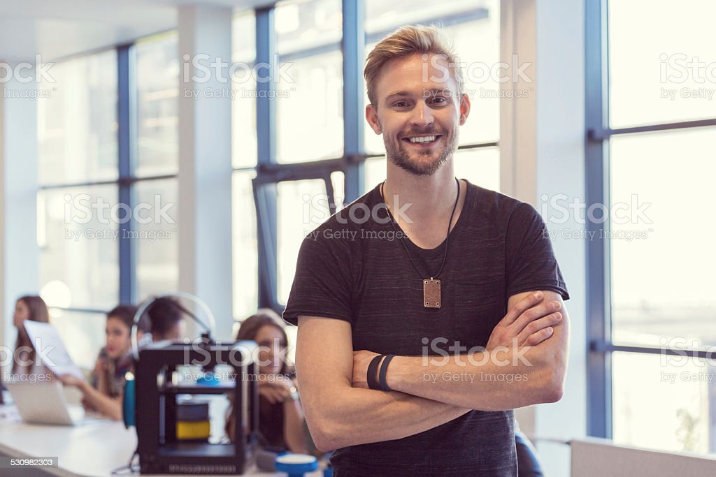 Young man in 3D printer office Start-up Business. Focus on confident young man smiling at camera with group of people using 3D printer in the background. 2015 Stock Photo