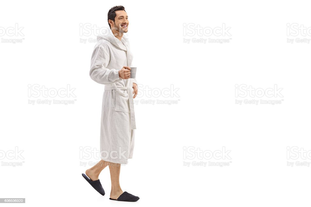 Young man in a bathrobe holding a cup and walking – Foto
