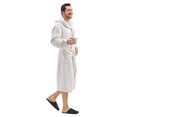 young man in a bathrobe holding a cup and walking - accappatoio foto e immagini stock
