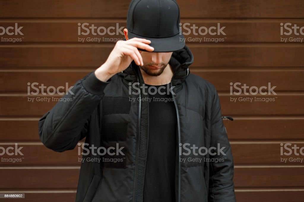 young man in a black fashionable baseball cap and a winter warm jacket posing on the street stock photo