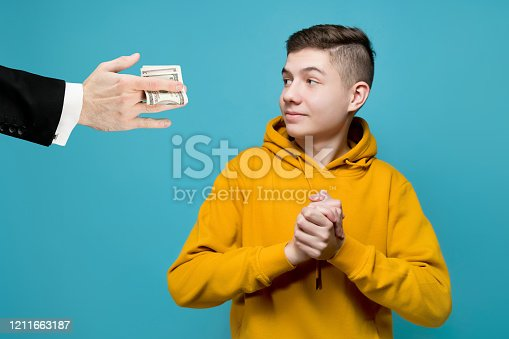 A young man in a bright sweatshirt rejoices that a business man gives him money. Men's hands in jackets hold out dollars to a teenager, he smiles. The boy born with a silver spoon in his mouth