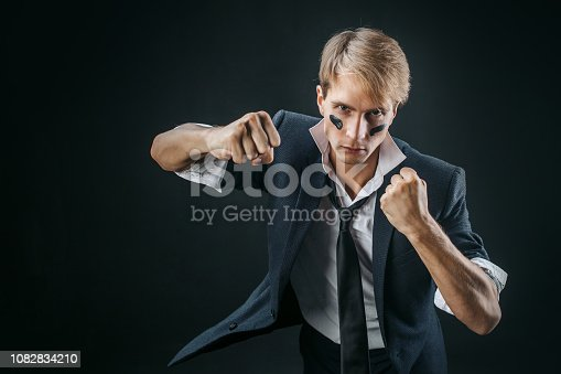 istock A young man in a business suit rolled up his sleeves and Boxing. Aggressive business, concept. Businessman 1082834210