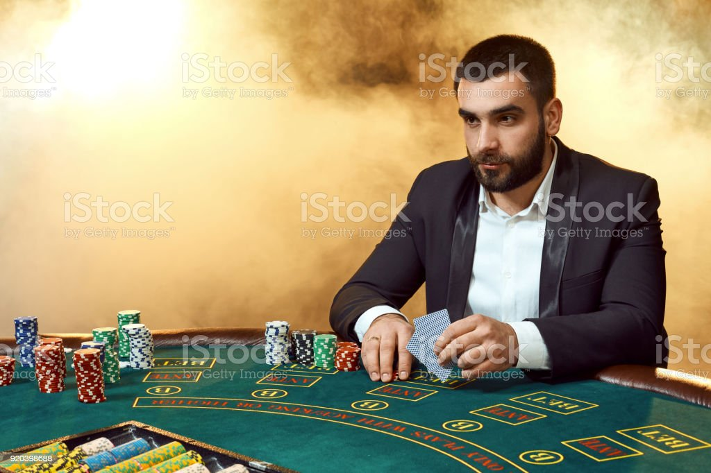 A young man in a business suit sitting at the poker table. Man gambles. The player at the gaming table playing cards stock photo
