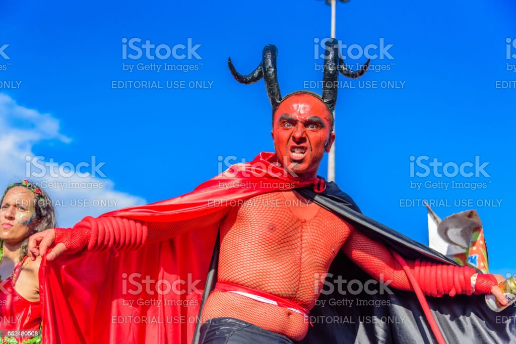Young man in a costume of devil with red face, black horns and cloak walking on stilts at Bloco Orquestra Voadora, Carnaval 2017 stock photo