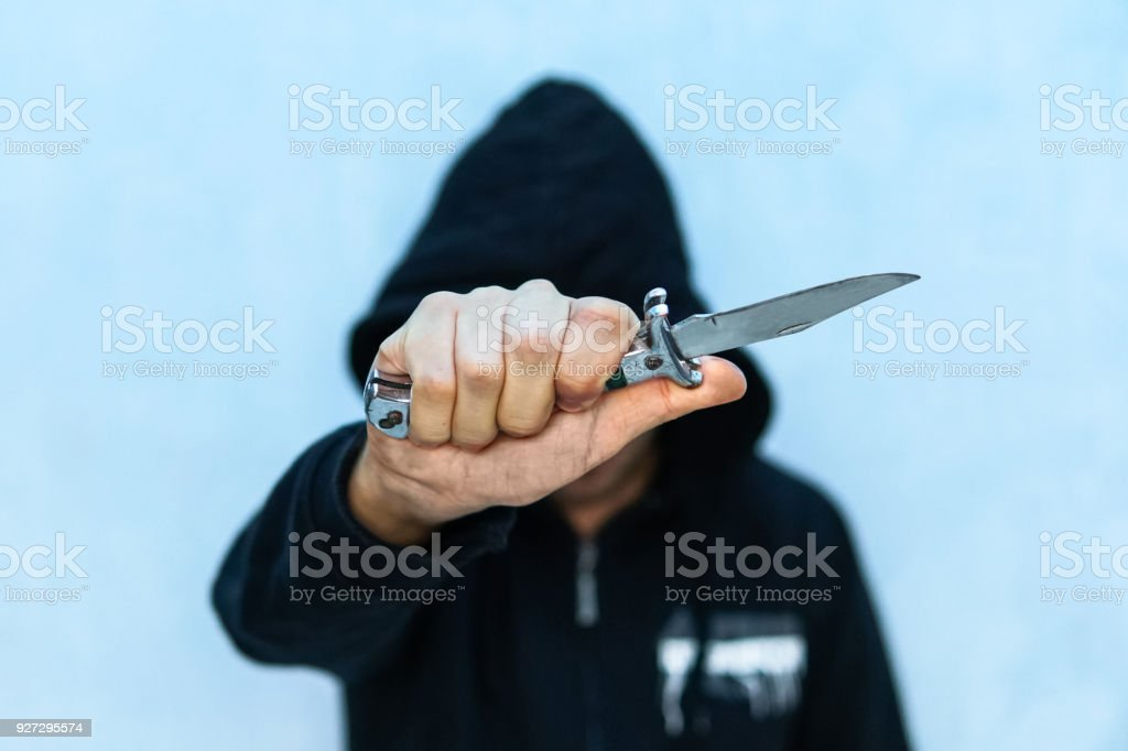 A young man in a hoodie holding stock photo