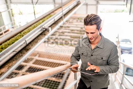 Young caucasian man using a digital tablet in a hops drying hall.
