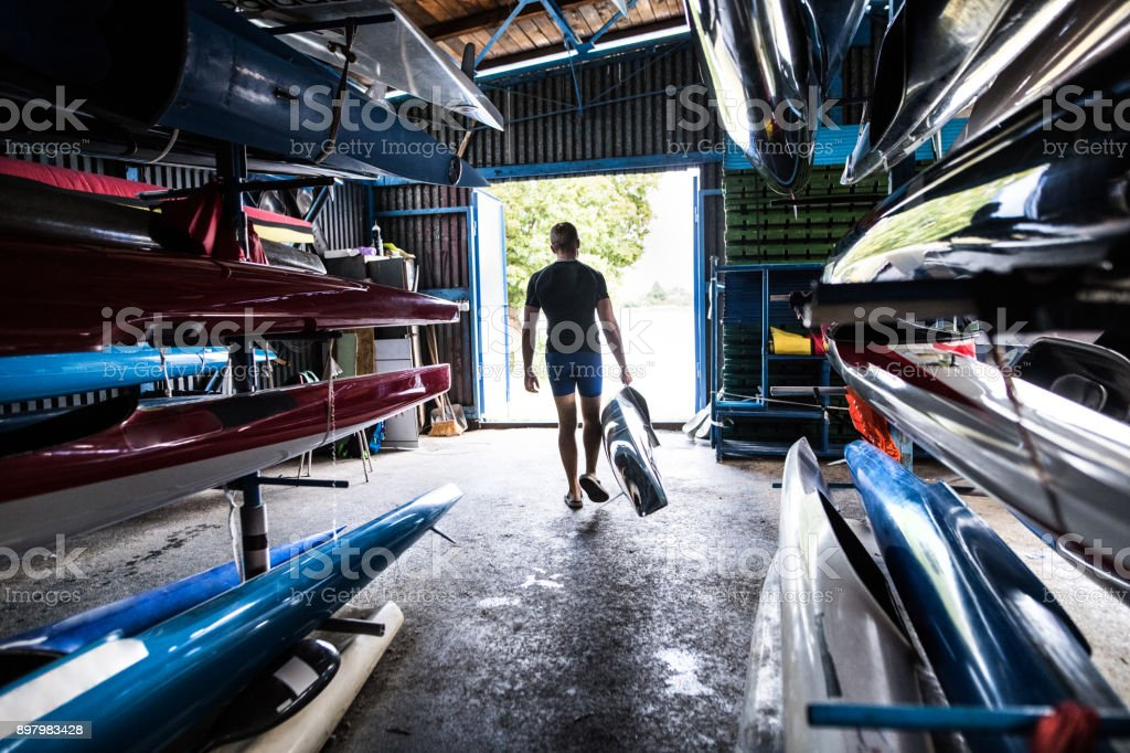 Young man in a kayak and canoe storage room. stock photo