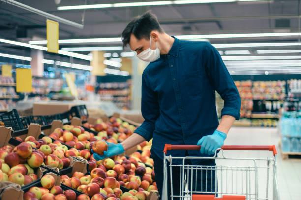 junger Mann in einer Schutzmaske, die mit Äpfeln in der Nähe des Tresens steht – Foto