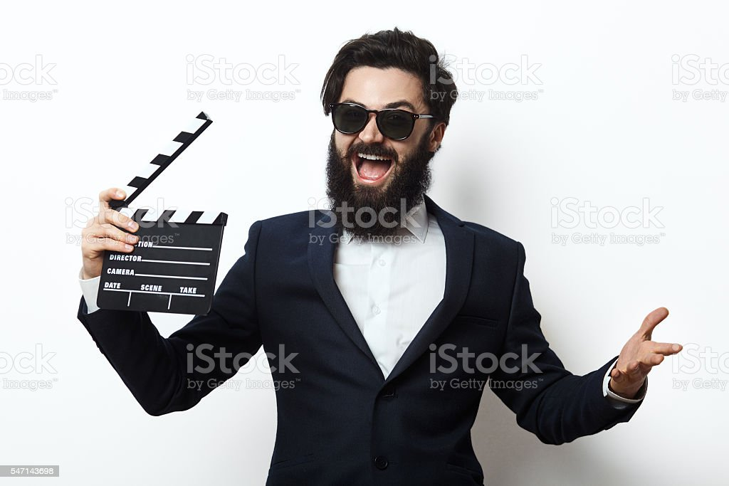 Young man in a suit holding movie clapperboard stock photo