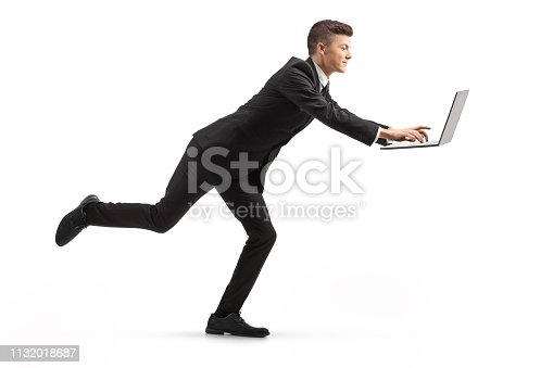 istock Young man in a suit running and using a laptop computer 1132018687