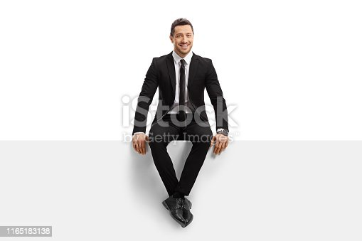 Full length portrait of a young man in a suit sitting on a panel and smiling isolated on white background