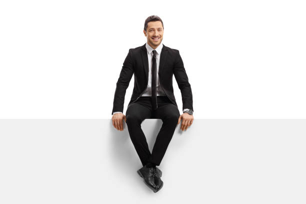 Young man in a suit sitting on a panel and smiling Full length portrait of a young man in a suit sitting on a panel and smiling isolated on white background sitting stock pictures, royalty-free photos & images