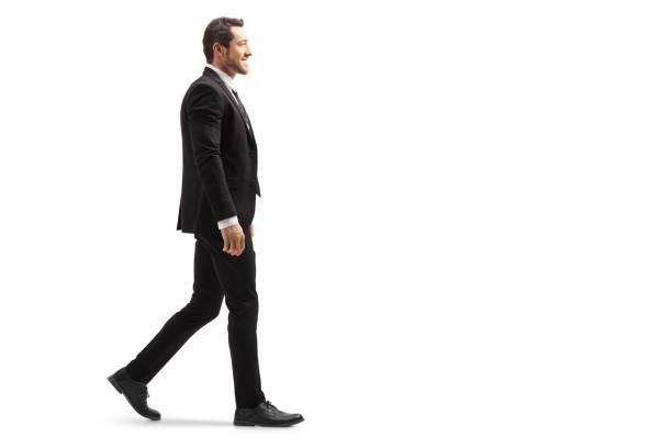スーツを着た若い男が歩いて微笑んでいる - 歩く ストックフォトと画像