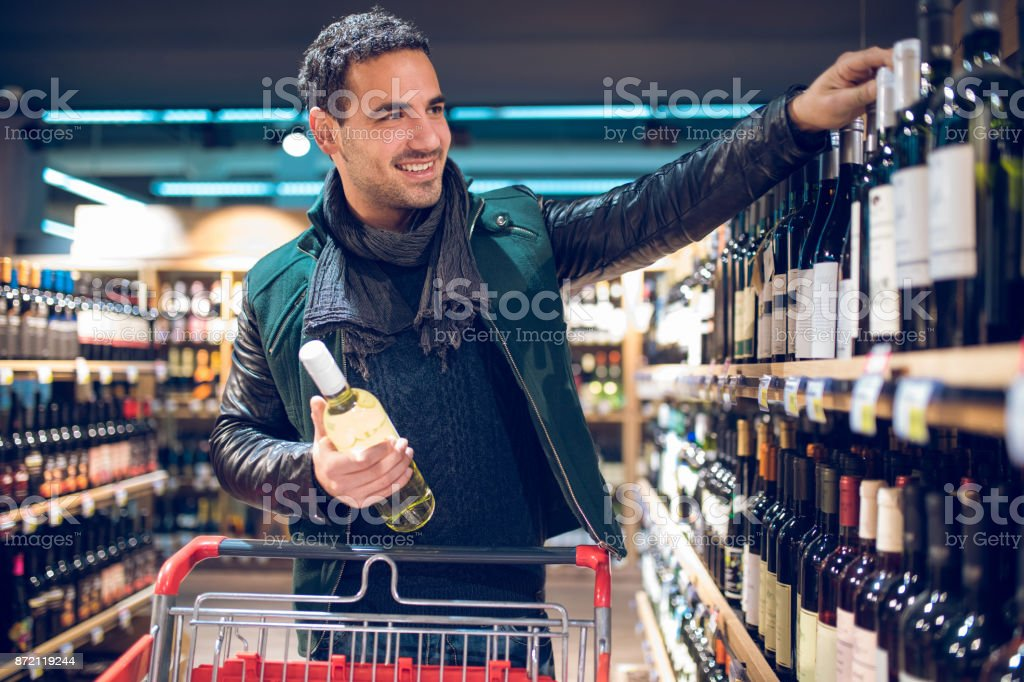 Young man in a supermarket choosing wine stock photo