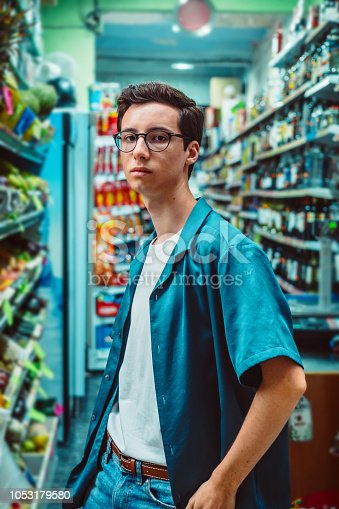 Young man in a supermarket. He is wearing a blue shirt and.