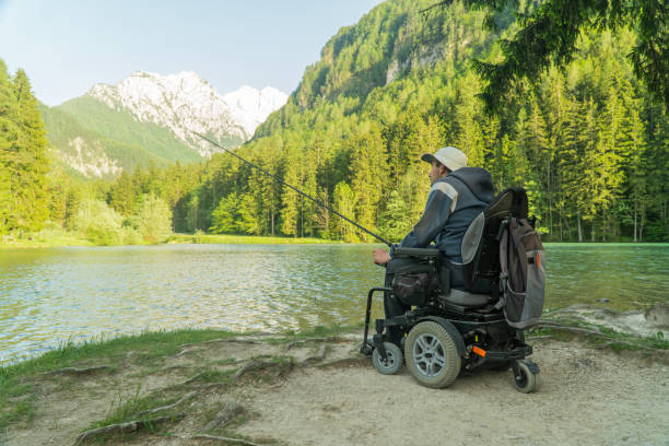 young man in a wheelchair fishing at the beautiful lake on a sunny day, with mountains in the back stock photo