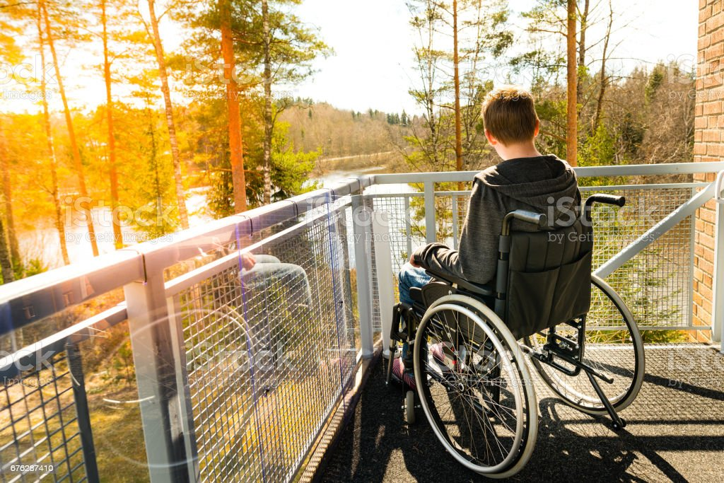 Young man in a wheelchair looking at the nature stock photo