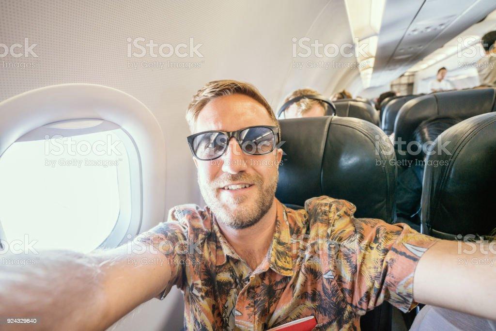 Junger Mann im Flugzeug nimmt Handy Selfie Porträt während des Fluges – Foto