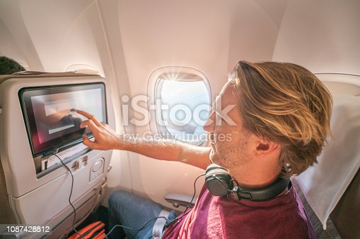 istock Young man in airplane using onboard entertainment 1087428812