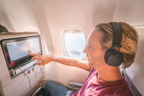 Junger Mann im Flugzeug mit onboard-entertainment – Foto