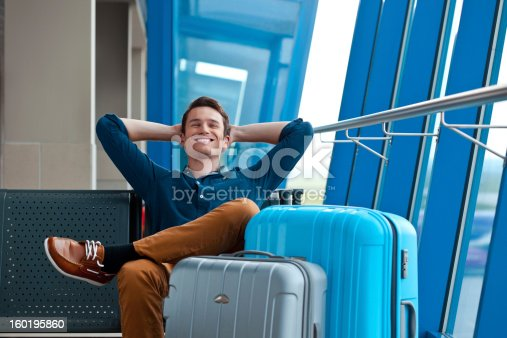 Cheerful young adult man waiting for his flight at the airport lounge, relaxing with hands behind head.