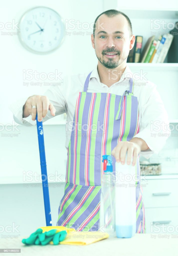 Young man in apron cleaning table stock photo
