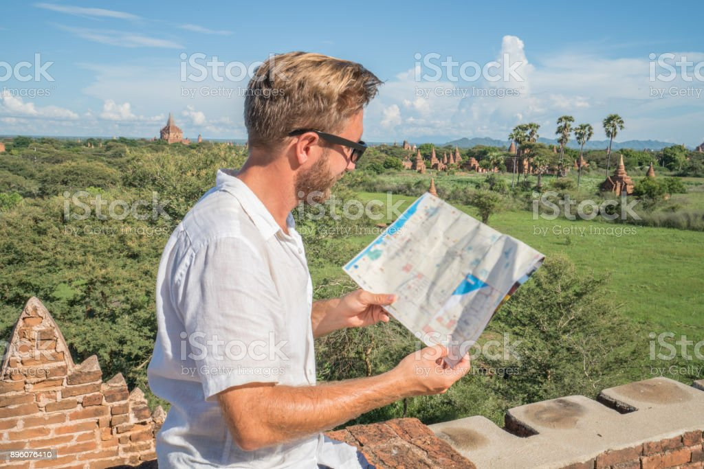 Caucasian young man looking at the Bagan archeological zone map,...